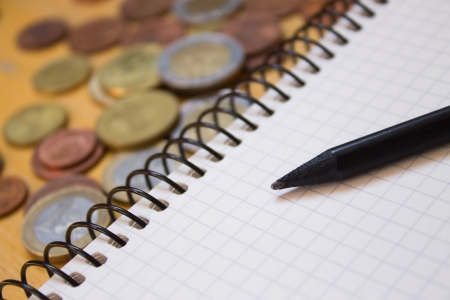 Black Pencil on white blank sheet of notebook near coins Stock Photo