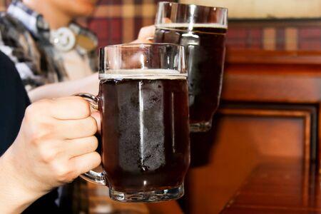 Glass of dark beer in hand photo