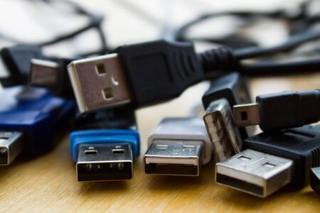 Many different USB cables on table Stock Photo