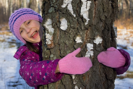 happy small girl hug tree in winter snowy forest photo