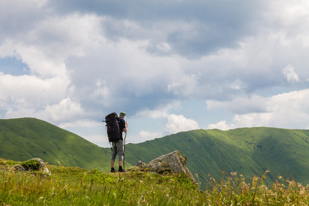 a man with backpack in mountains