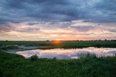 Beautiful sunset landscape over small rural lake