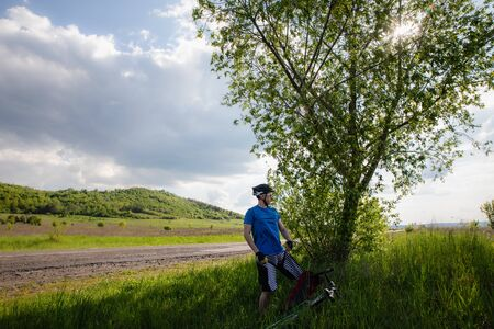 Man with bicycle in full cycling equipment with helmet, blue t-shirt in green summer field near tree and road, active healthy lifestyle in nature envirment copy space