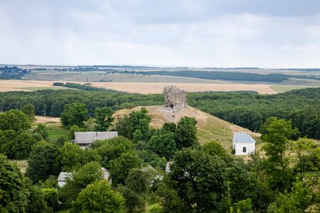 Scenic view on Pidkamin inselberg on adjacent hill and nearby village in Brody region of Galychyna, Ukraine