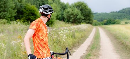 Man with bicycle in full cycling equipment with helmet, orange t-shirt in green summer field looking at road, active healthy lifestyle in nature envirment banner copy space Foto de archivo