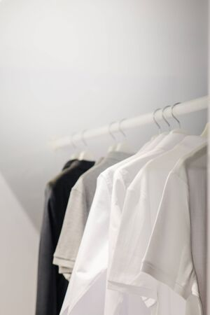 White t-shirts hanging in dresser, black, grey cloth in clothet, clean laundry white background copy space