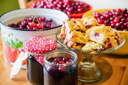 Jars of tasty summer cherry jam with baked cherry cake and raw cherries background