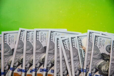 Stack of hundreds of dollars on bright green background with copy space