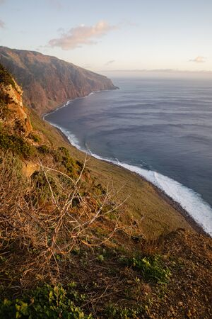 Beautiful scenic sunset view on cliffs coast of Atlantic Ocean with blue breaking waves in Madeira island Foto de archivo