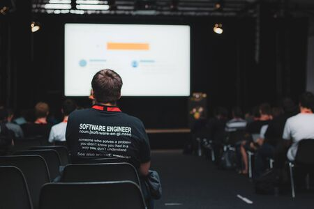 Software engineer in black t-shirt sitting in conference hall during programming worshop in full hall with audience learning programming
