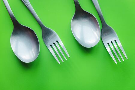Metal forks and spoons cutlery on green background flat lay