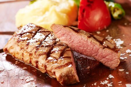 side dish: grilled steak and side dish on a wooden plate