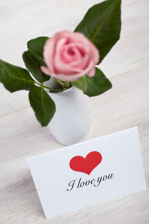 Single pink rose in porcelain vase on wooden table Stock Photo - 4272477
