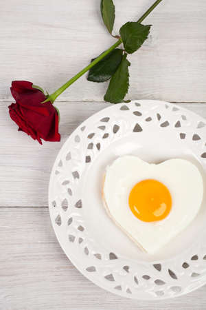 Heart shaped fried egg on beautiful plate with roses