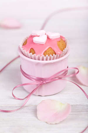 satin ribbon: Pink cupcakes in pink cup with satin ribbon and heart shaped decorations Stock Photo