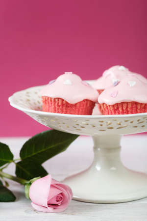 Pink cupcakes with cream cheese frosting pn cake plate. Country living style. Stock Photo - 4272476
