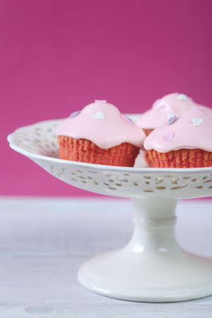 Pink cupcakes with cream cheese frosting pn cake plate. Country living style. Stock Photo - 4272470