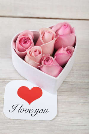 Pink roses with a card written saying love you photo