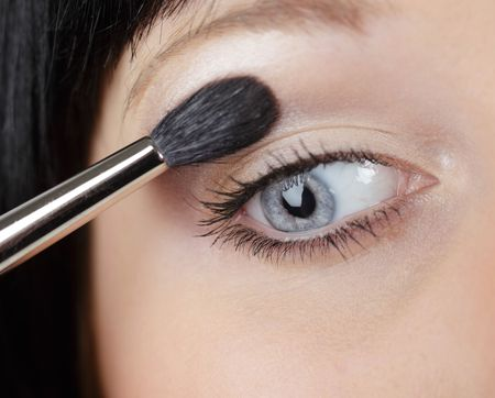 Young Caucasian woman with light skin and black hair applying eye shadow photo