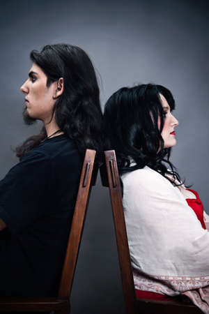 Young caucasian couple with long black hair sitting back to back after a conflict photo