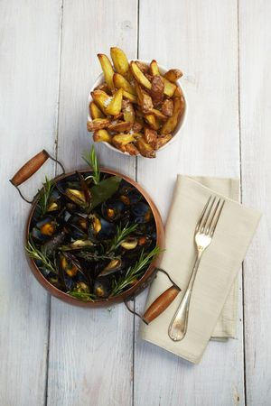 Common mussels in a copper cooking pot with French fries spiced with sea salt. There is nobody viewable in the image photo