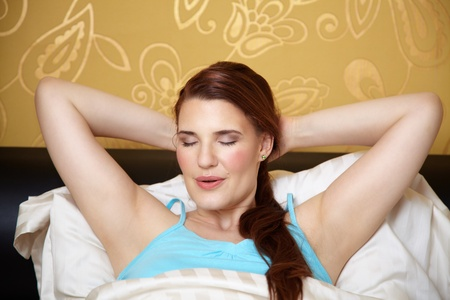 Woman in bed stretching her arms behind her head. She is breathing slowly and relaxing photo