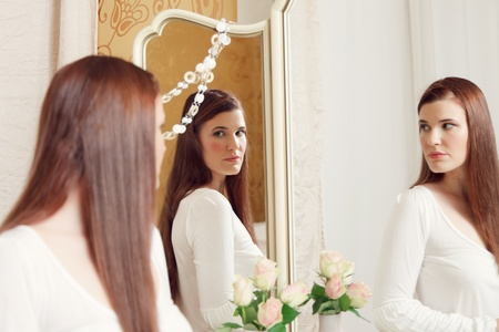 Attractive brunette woman sitting in front of a dressing table looking into the mirror photo