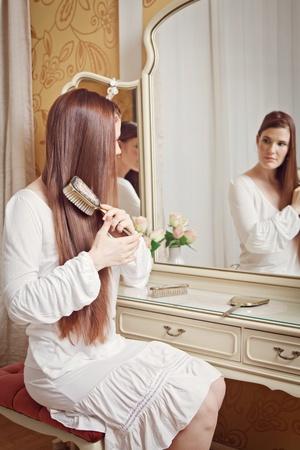 spiegelbeeld: Aantrekkelijke brunette vrouw zit achter een kaptafel kijken in de spiegel en haar haar borstelt Stockfoto