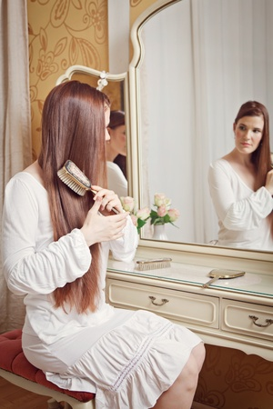 Attractive brunette woman sitting in front of a dressing table looking into the mirror and brushing her hair photo