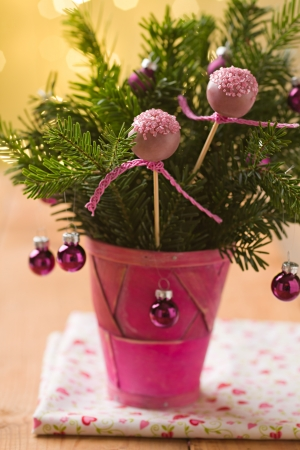 Pink cake pops with ribbon in Christmas decoration bouquet with pink baubles and some spruce photo