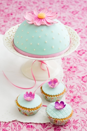 Round cake and three cupcakes decorated with fondant and gum paste flowers photo