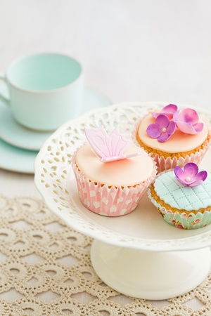 Three cupcakes decorated with fondant and gum paste flowers photo