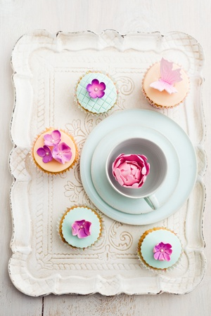 Cupcakes decorated with fondant and gum paste flowers and a butterfly photo