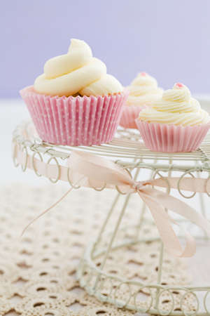Three vanilla cupcakes with buttercream swirl topping on vintage cake stand photo