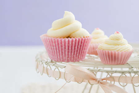 buttercream: Three vanilla cupcakes with buttercream swirl topping on vintage cake stand Stock Photo