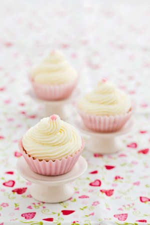 buttercream: Three vanilla cupcakes with buttercream swirl topping on mini cake stands