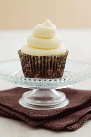 Single vanilla cupcake with buttercream swirl topping on a small cake stand photo