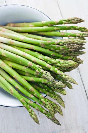 asperges: Verse ongekookte groene asperges in een kom
