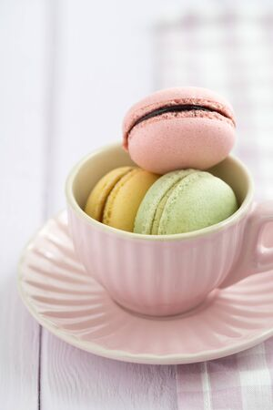 Colourful macarons in a rosy cup