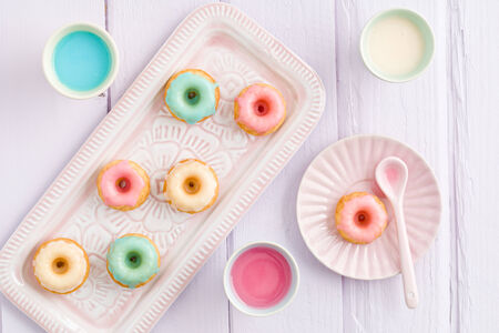 Iced mini bundt cakes with icing, a tray and a spoon Banco de Imagens