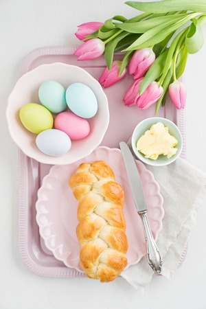 Easter breakfast table with Easter eggs, tulips and sweet yeast braided bread
