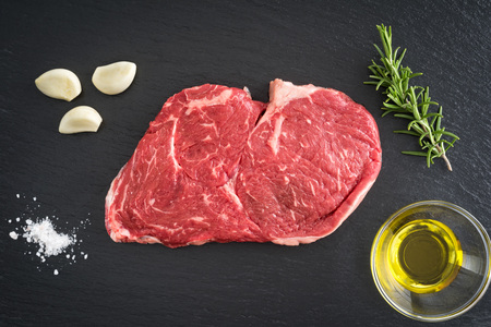 Fresh uncooked rib-eye steak with garlic, salt, olive oil and rosemary on black background