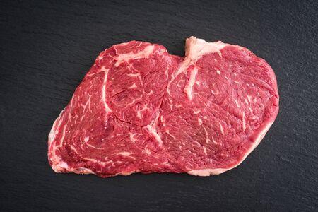 Fresh uncooked rib-eye steak on black background
