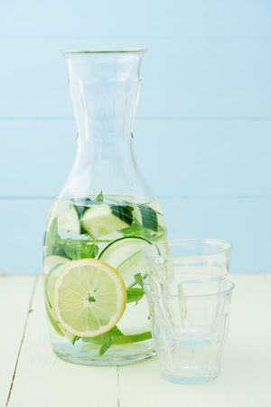 Infused water with cucumber, lemons and mint in a pitcher Banco de Imagens