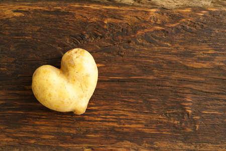Hear shaped potato and potato on dark wood Banco de Imagens