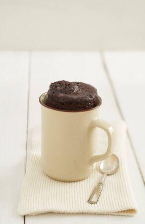 Simple chocolate mug cake in a mug on beige Banco de Imagens