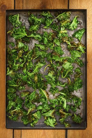 Kale chips with sea salt on a an rustic baking tray