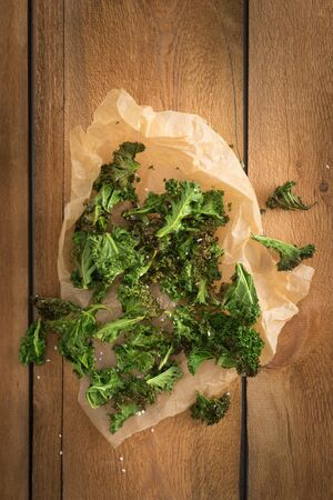 Kale chips with sea salt in parchment paper on wooden table