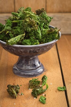 Kale chips with sea salt in a small dark serving bowl