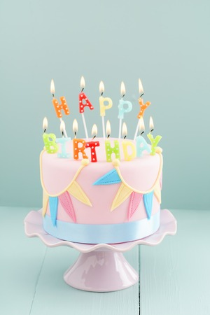 Fondant covered pastels coloured birthday cake with happy birthday candles